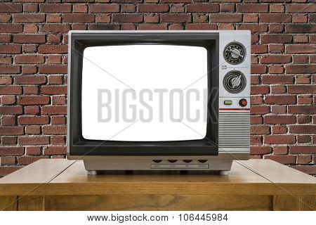 Vintage portable television with red brick wall and cut out screen.