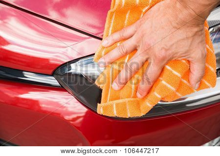 Male Worker Cleaning Car Headlight