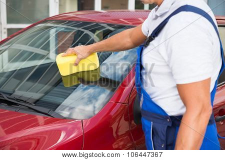 Worker Cleaning Car Windshield With Sponge