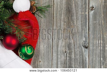 Santa Cap With Ornaments And Evergreen Branch On Wooden Boards