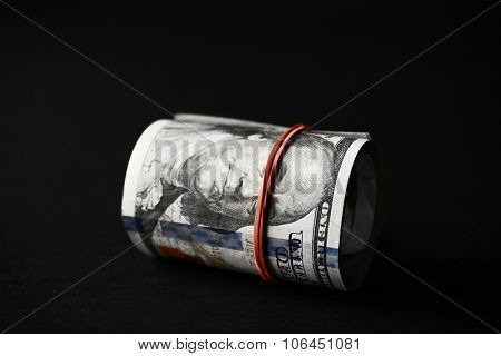 Dollars roll on black background