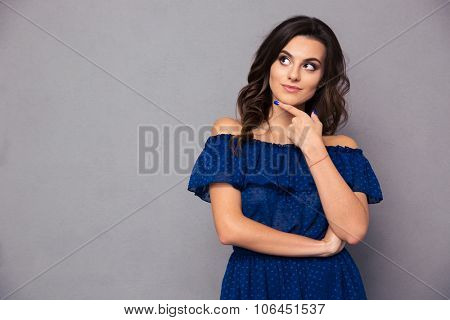 Portrait of a happy thoughtful woman looking away over gray background
