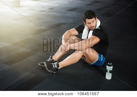 Sportsman wearing blue shorts and black t-shirt sitting on the floor in gym