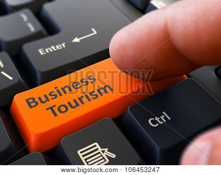 Pressing Orange Button Business Tourism on Black Keyboard.