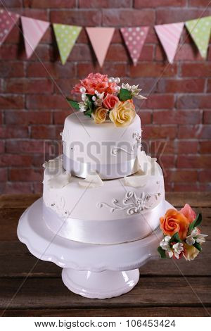 Beautiful wedding cake decorated with flowers on wooden table against brick wall background