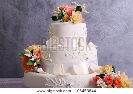 White wedding cake decorated with flowers on grey background
