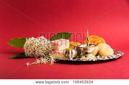 Beautifully Decorated Pooja Thali for diwali celebration to worship , having Indian sweets, silver l