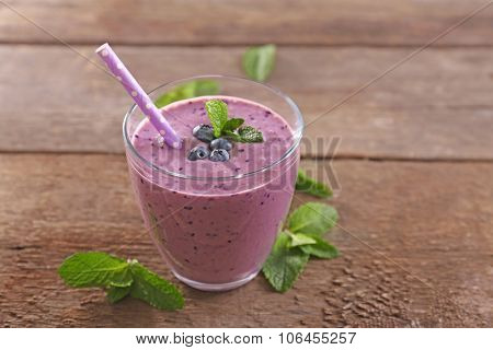 Tasty blueberry yogurt decorated with berries and mint on wooden background