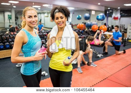 Fit women chatting in weights room at the gym