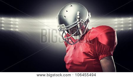 American football player looking down against spotlight