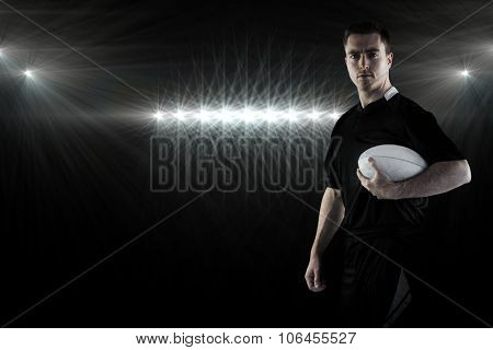 Rugby player holding a rugby ball against spotlight