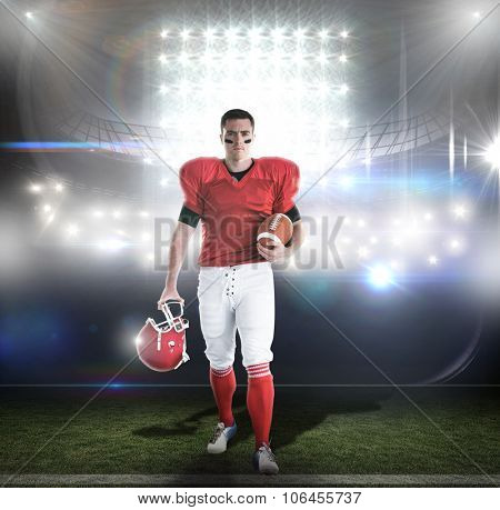 Portrait of american football player walking and holding football and helmet against american football arena