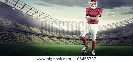 Portrait of american football player with arms crossed against rugby stadium