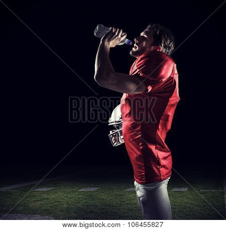American football player in red jersey holding helmet while drinking water against black