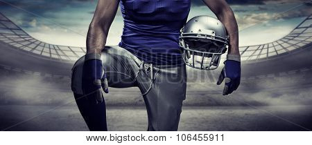 Mid section of sportsman holding helmet against rugby stadium