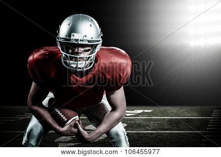 Portrait of American football player bending while holding ball against spotlight