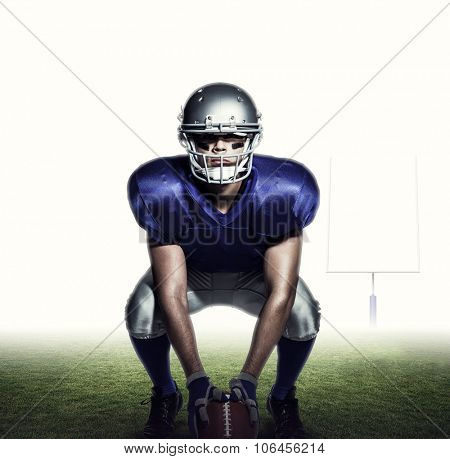American football player with ball crouching against american football posts