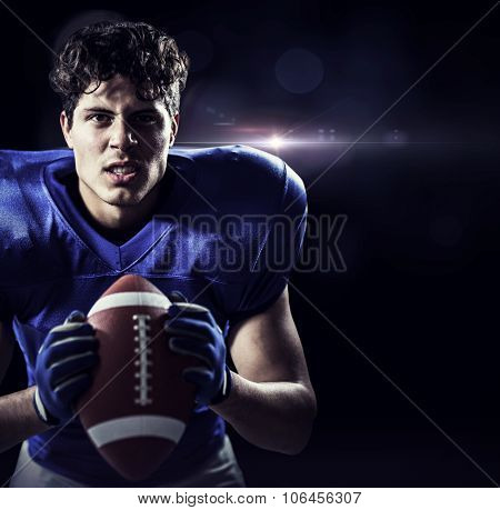 Portrait of aggressive American football player against black