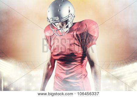 American football player looking down while standing against rugby stadium