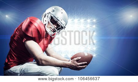 Portrait of American football player crouching while holding ball against spotlight