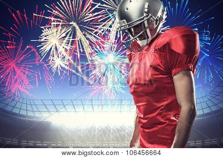American football player in red jersey looking down against fireworks exploding over football stadium