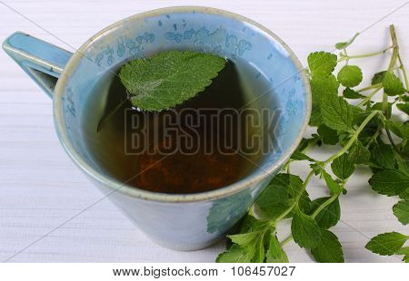 Fresh Lemon Balm And Cup Of Herbal Drink On White Wooden Table
