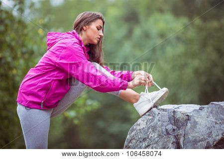 Fit woman tying her shoelace in the countryside