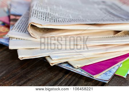 Newspapers and magazines on old wood background.