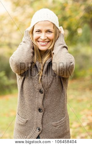 Smiling pretty woman with hat on an autumns day