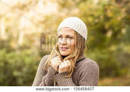 Pretty woman holding her scarf on an autumns day