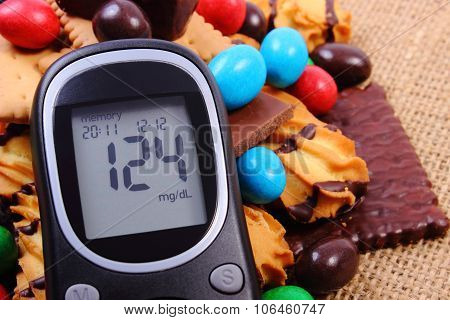 Glucometer With Heap Of Sweets On Jute Burlap, Diabetes And Unhealthy Food