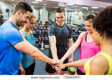 Fit people putting their hands together at the gym