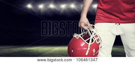 American football player holding a helmet against rugby stadium