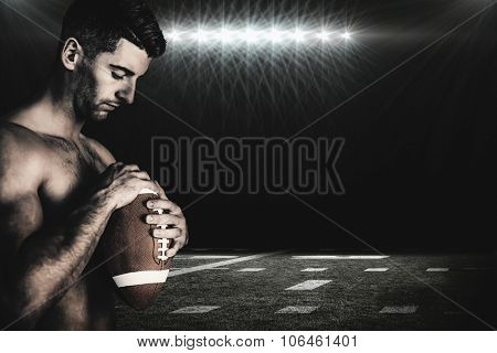 Rugby player holding the ball while looking down against spotlight