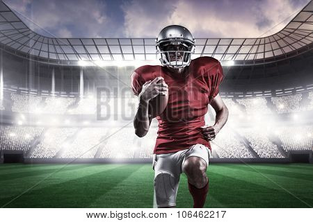 Full length of American football player in red jersey running against rugby stadium