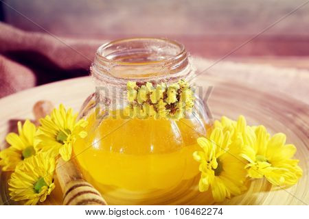 Honey with flowers and dipper on wooden tray on table