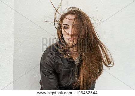 Sad girl with long hair in leather jacket