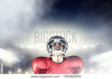 American football player holding ball while looking up against rugby stadium