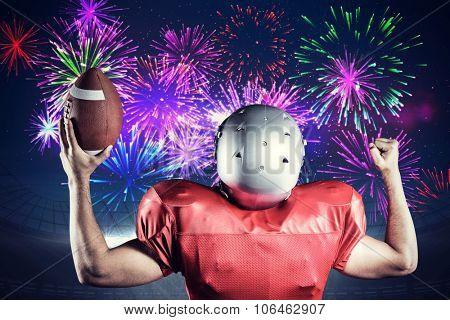 Rear view of American football player cheering while holding ball against fireworks exploding over football stadium