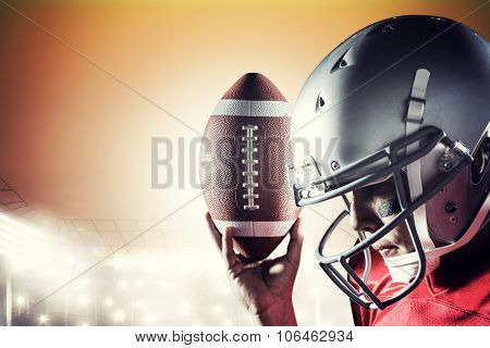 Sportsman looking down while holding American football against rugby stadium