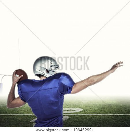 Rear view of American football player throwing ball against american football posts