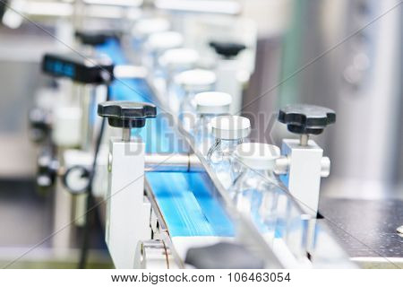 pharmaceutical industry. Production line machine conveyor with glass bottles ampoules at factory, Shallow DOF