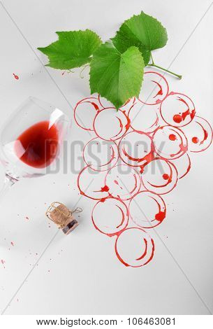 Spots made with wine cork and goblet of spilled wine isolated on white