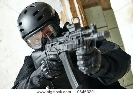 military industry. Portrait of special forces or anti-terrorist police soldier, private contractor armed with assault rifle ready to attack during clean-up operation, mission