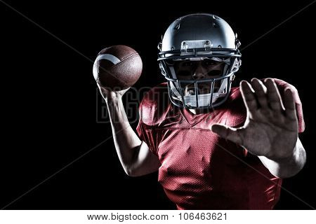 Portrait of sportsman defending while holding American football against black