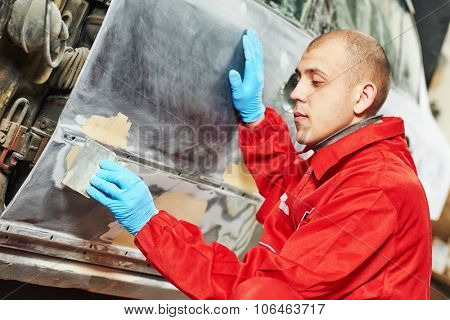 auto mechanic worker applying car body filler at automobile repair and renew service station
