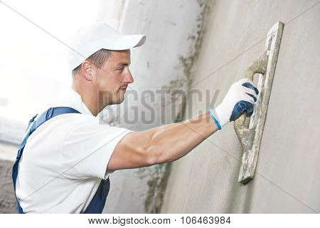 Male plasterer at indoor wall renovation decoration with putty knife float
