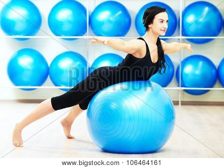 young woman doing stretching on fitness ball during pilates exercises in sport club