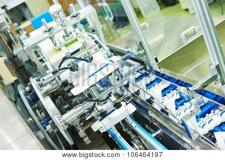 pharmaceutical industry. Line machine conveyer for packaging glass bottles ampoules in boxes at pharmacy factory