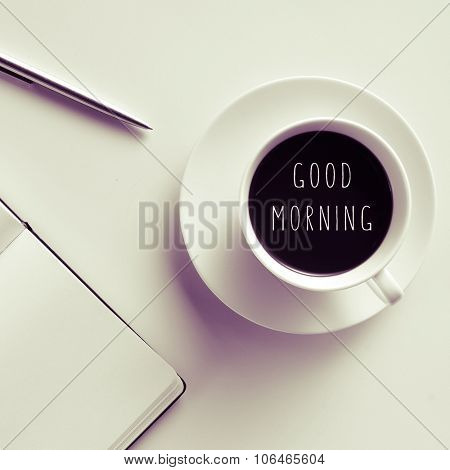 high-angle shot of a white table with a pen, a notebook, and a cup of coffee with the text good morning written in it